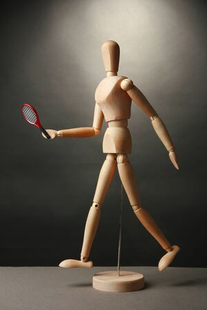 Wooden mannequin with tennis racket on grey background photo