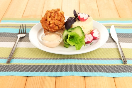 Chicken Kiev on croutons with mashed potatoes, on wooden background photo