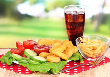 Fried chicken nuggets with french fries,cola,vegetables and sauce on table in park photo