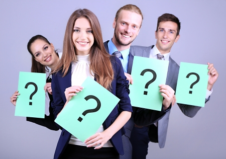 Business team standing in row with question mark on grey background photo