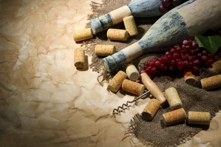 Old bottles of wine, grapes and corks on old paper background