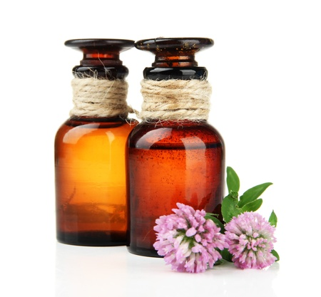 Medicine bottles with clover flowers, isolated on white photo