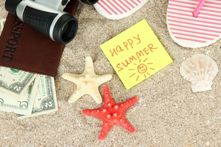 Composition with flip flops, binoculars, notepad and money, on sand background photo