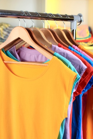 Variety of casual t-shirts on wooden hangers on shelves background photo