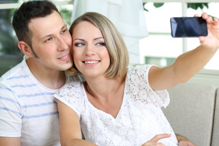 Young couple  taking  photo with  mobile phone in restaurant photo