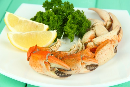 Boiled crab claws on white plate with salad leaves ,on wooden table background photo