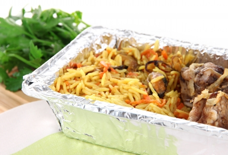 Food in box of foil on napkin on wooden board isolated in white photo