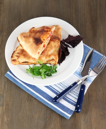 Pizza calzone on plate on napkin on wooden table photo