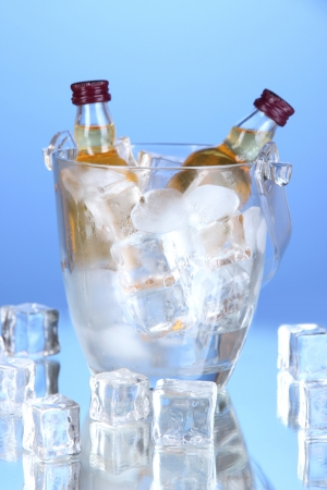Minibar bottles in bucket with ice cubes,  on color background photo
