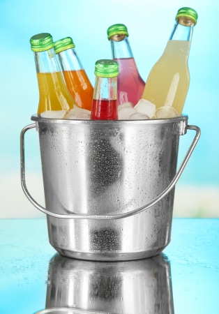Bottles with tasty drinks in bucket with ice cubes, in bright background photo