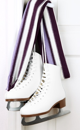 Figure skates hanging on a door knob with scarf photo