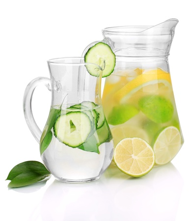 Cold water with lemon, cucumber and ice in pitchers isolated on white photo