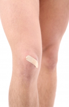 Young man with adhesive bandage on knee, isolated on white photo
