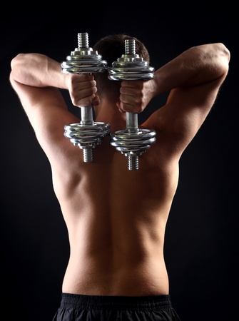 Handsome young muscular sportsman execute exercise with dumbbells on dark background photo