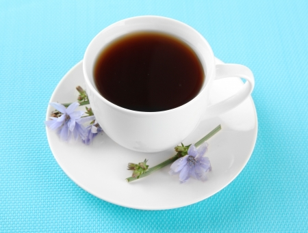 Cup of tea with chicory, on blue background photo