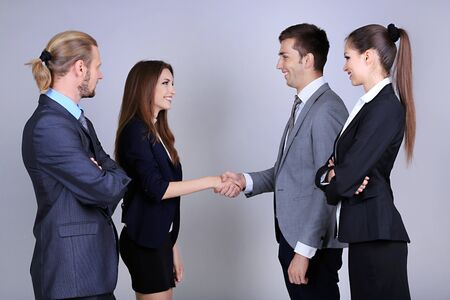 introducing: Business colleagues introducing with handshake, on grey background