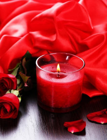 Beautiful romantic red candle with flowers and silk cloth, close up photo