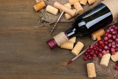 Bottle of wine, grapes and corks on wooden background photo