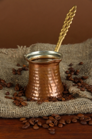Metal turk and coffee beans on brown background photo