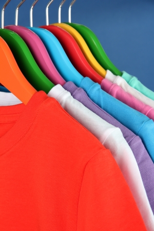 Different shirts on colorful hangers on blue background photo