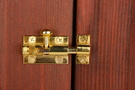 Metal latch in wooden door close-up photo