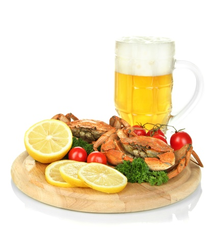 Boiled crabs with lemon slices and tomatoes, on wooden board, isolated on white photo
