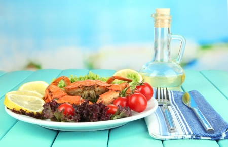 Boiled crab on white plate with salad leaves and tomatoes,on wooden table, on bright background photo