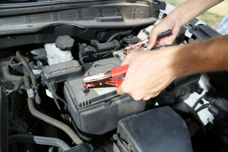 Car mechanic uses battery jumper cables to charge dead battery Stock Photo - 21552864