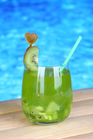 Tasty cocktail on swimming pool background photo