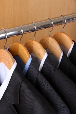 Suits with shirts on hangers on wooden background photo