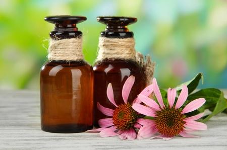 purpurea: Medicine bottles with purple echinacea flowers on wooden table, outdoors