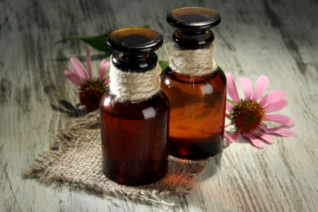 Medicine bottles with purple echinacea flowers on wooden table photo