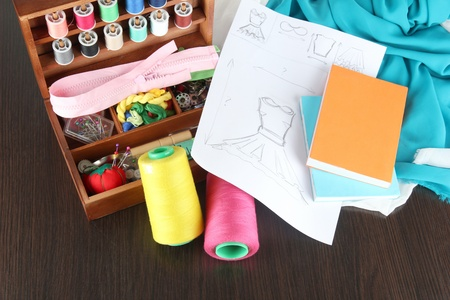sewing box: Sewing kit in wooden box,cloth and sketch on wooden table