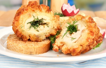 Chicken Kiev on croutons with mashed potatoes, on wooden table, on bright background photo