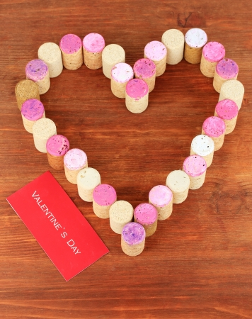 Wine corks laid out in form of heart on wooden table close-up photo