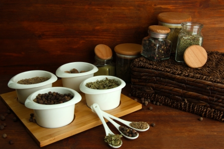 Assortment of spices in  white spoons and bowls, on wooden background photo