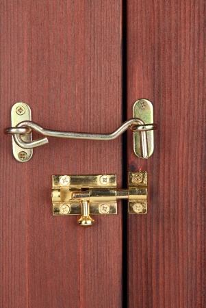 Metal hook and deadbolt in wooden door close-up photo
