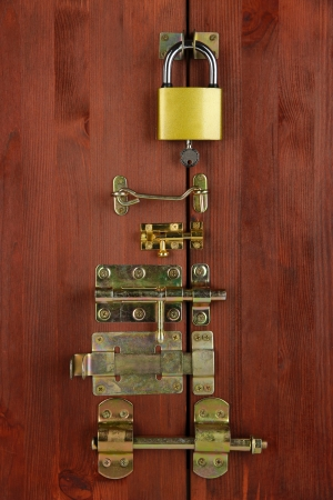 deadbolt: Metal bolts, latches and hooks in wooden door close-up