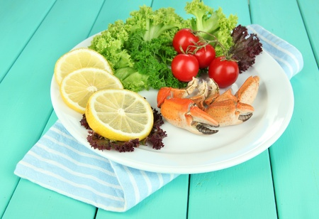 Boiled crab claws on white plate with salad leaves and tomatoes,on wooden table background photo