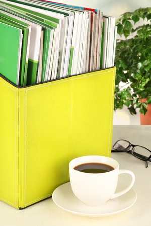 Magazines and folders in green box,on office interior background photo