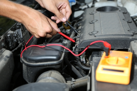 Auto mechanic uses multimeter voltmeter to check voltage level in car battery photo