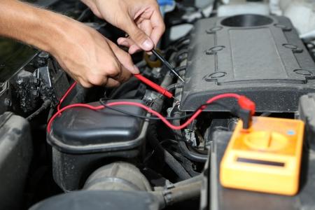 Mécanicien automobile utilise multimètre voltmètre pour vérifier le niveau de tension dans la batterie de voiture Banque d'images