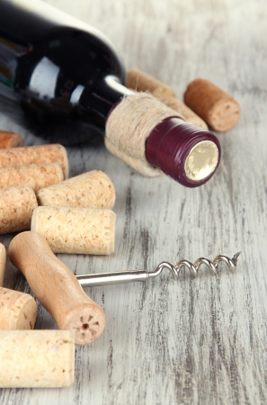 binge: Corkscrew with wine corks and bottle of wine on wooden table close-up