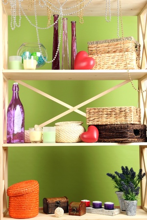 Beautiful white shelves with different home related objects, on color wall background Stock Photo - 21648944