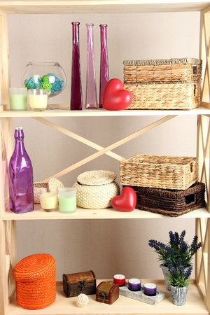 Beautiful white shelves with different home related objects, on color wall background photo