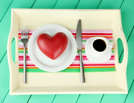 Wooden tray with breakfast, on color wooden background photo
