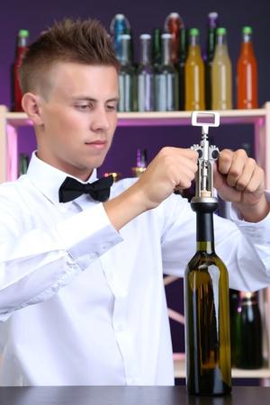 opens: Bartender opens bottle of wine Stock Photo