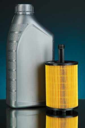 Car oil filter and motor oil can on dark color background photo