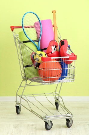 karemat: Shopping cart with sport equipment, on green wall background