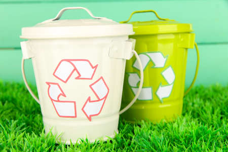 Recycling bins on green grass on color wooden background photo